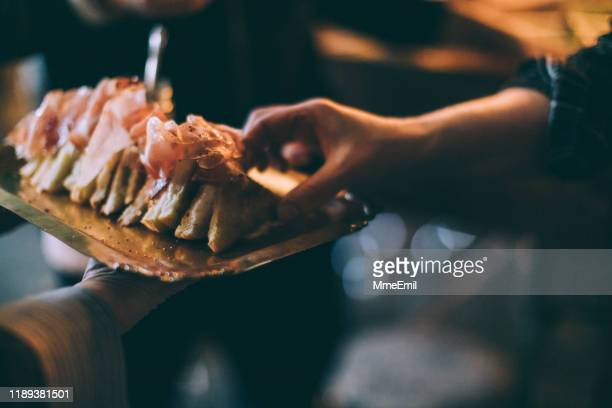 eating grilled cheese sandwich during a party - mmeemil stock photos and pictures
