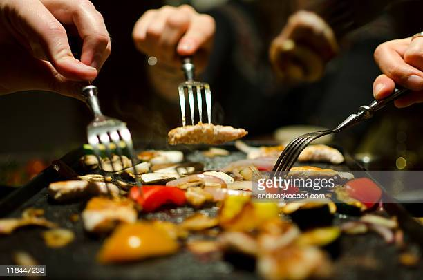 Eating grilled meat and raclette