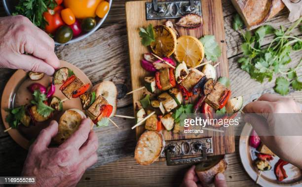 eating grilled vegan tofu and vegetable skewers - vegetarianism stock pictures, royalty-free photos & images