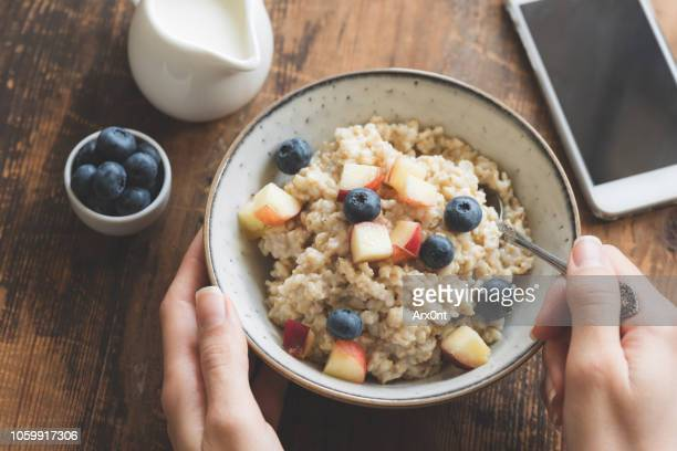 eating healthy breakfast. oatmeal porridge in bowl - oatmeal stock photos and pictures