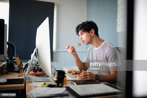 eating lunch at his desk - lunch stock pictures, royalty-free photos & images