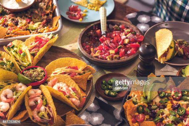 eating mexican tacos with spicy salsa and nacho tortilla chips - mexico stock photos and pictures