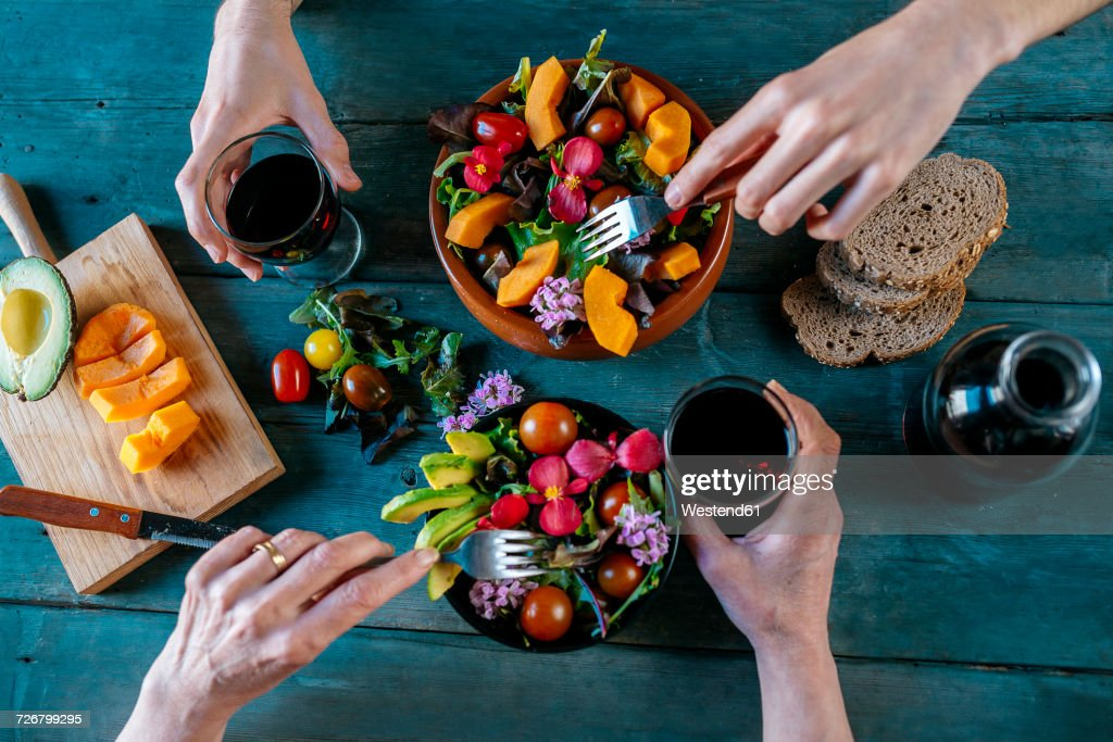 Eating mixed salads and drinking red wine : Stock Photo