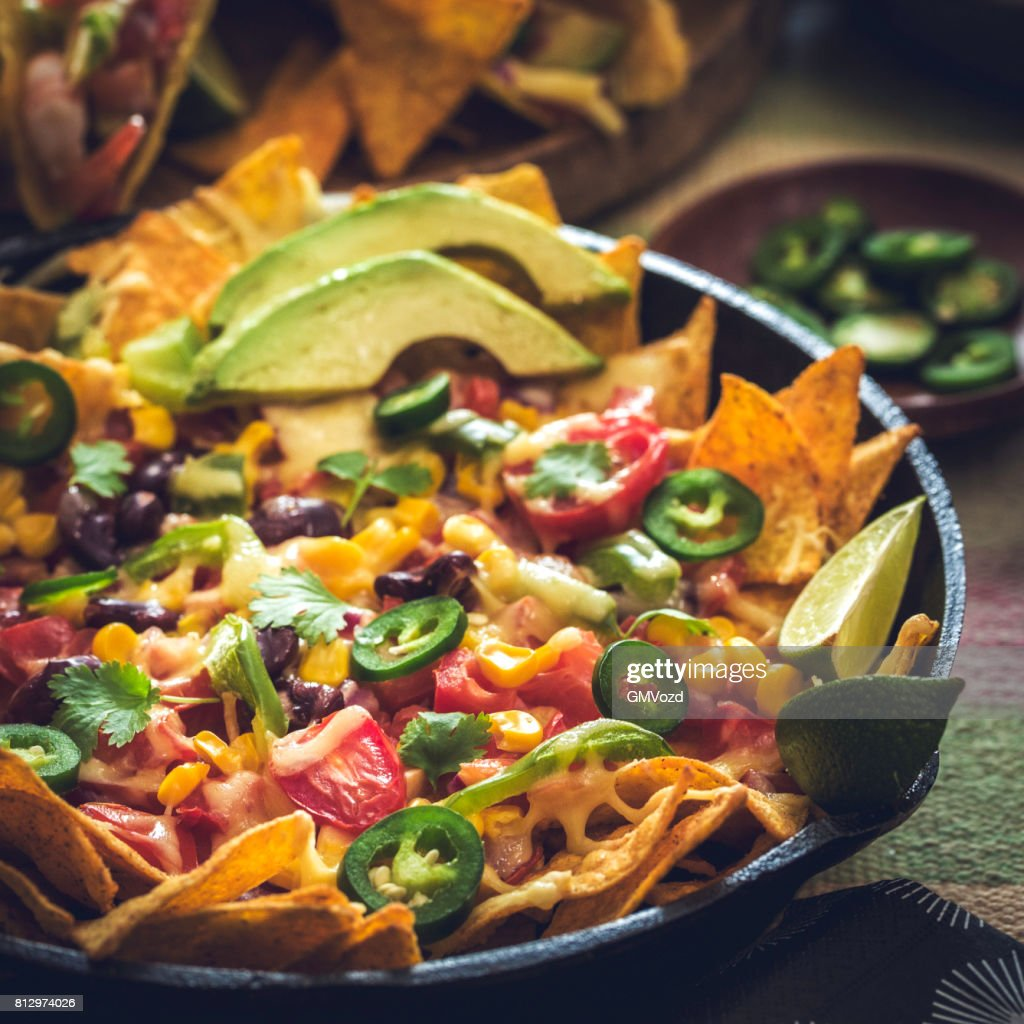 Eating Nachos Tortilla Chips with Salsa and Jalapenos : Stock Photo