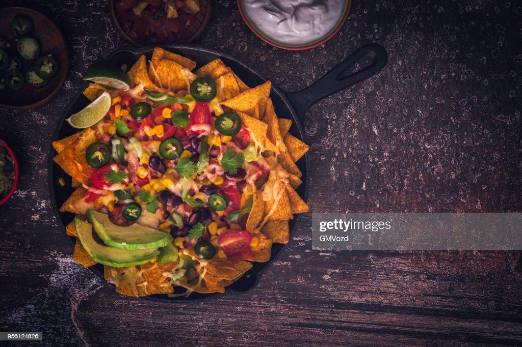 Comendo Nachos Tortilla Chips com Salsa e pimentões : Foto de stock