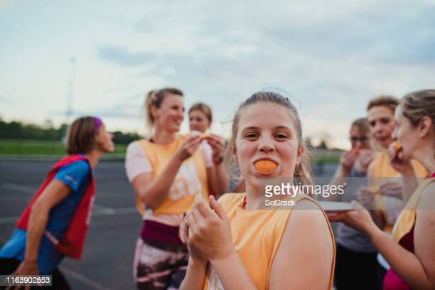 eating oranges after a netball game - team sport stock pictures, royalty-free photos & images