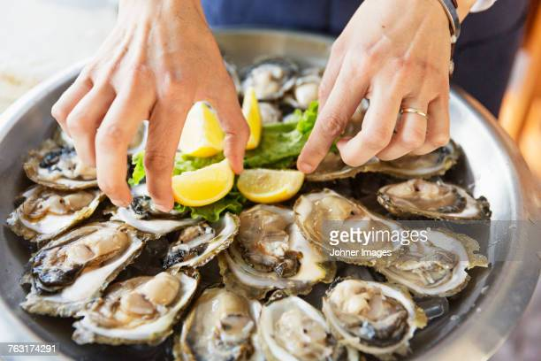 eating oysters, close-up - oyster shell stock photos and pictures