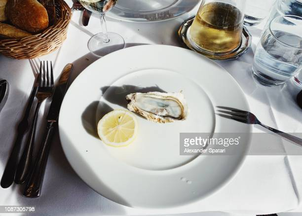 eating oysters in luxury french restaurant in paris, france - french cafe stock photos and pictures