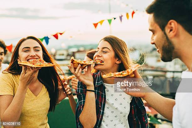 eating pizza at a party on the roof - large group of objects stock pictures, royalty-free photos & images