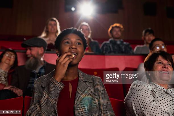 eating popcorn at the movies - film industry stock pictures, royalty-free photos & images