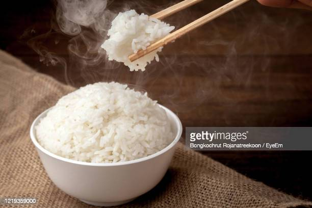eating rice by using chopsticks on wooden background - steamed stock pictures, royalty-free photos & images