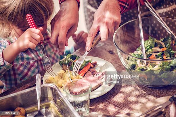 eating roast beef with potatoes and root vegetables - roast dinner stock pictures, royalty-free photos & images