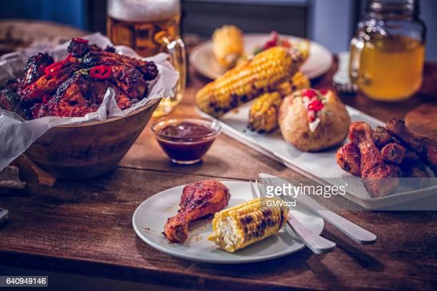 Essen Würzige Hühnerflügel mit gebackenen Kartoffeln und Mais