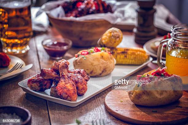 Eating Spicy Chicken Wings with Baked Potato and Corn