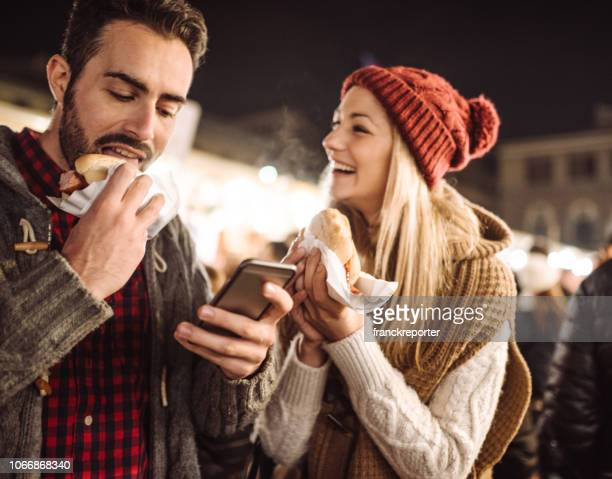 eating street food at the christmas markets in italy - sausage sandwich stock pictures, royalty-free photos & images