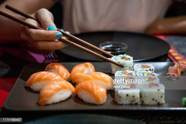 eating sushi with chopsticks in japanese restaurant. - wasabi stock pictures, royalty-free photos & images