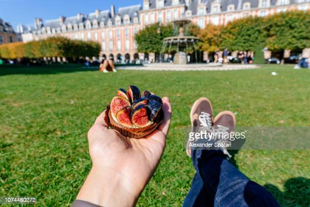 eating tartelette with fig while sitting on a green lawn in park in paris, france - subjektive kamera ungewöhnliche ansicht stock-fotos und bilder