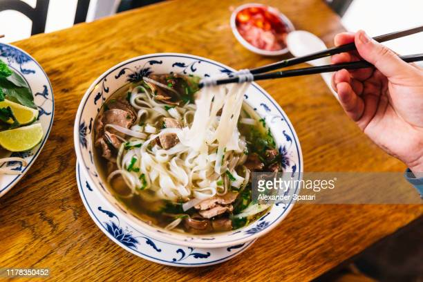 eating traditional vietnamese pho soup in a restaurant - beef stock pictures, royalty-free photos & images