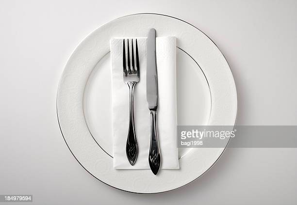 eating utensils on a white plate against a white background - stage set stock pictures, royalty-free photos & images