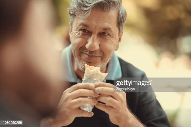 eating wrap - fast food - burrito stock pictures, royalty-free photos & images