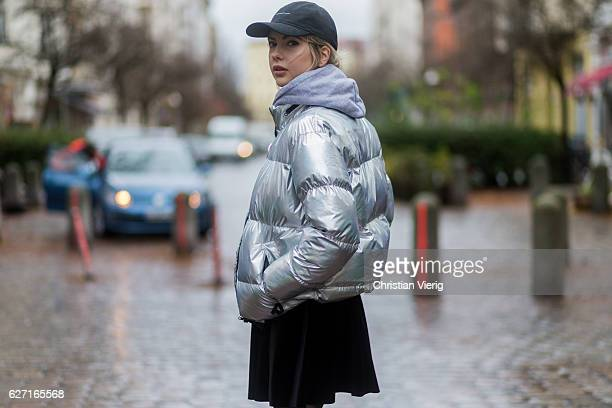 Ebba Zingmark wearing a silver down feather jacket from Bixtol a grey hoody and black cap from thatboii a black velvet mini skirt nobodys child HM...