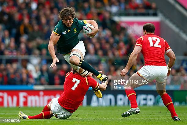 Eben Etzebeth of South Africa is tackled by Sam Warburton of Wales watched by Jamie Roberts of Wales during the 2015 Rugby World Cup Quarter Final...