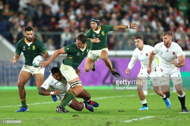 Eben Etzebeth of South Africa offloads the ball to teammate Damian de Allende as he is tackled by Manu Tuilagi of England during the Rugby World Cup...