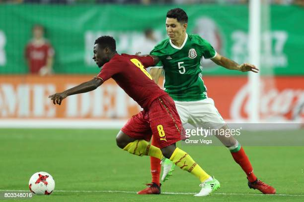 Ebenezer Ofori of Ghana fights for the ball with Jesus Molina of Mexico during the friendly match between Mexico and Ghana at NRG Stadium on June 28...