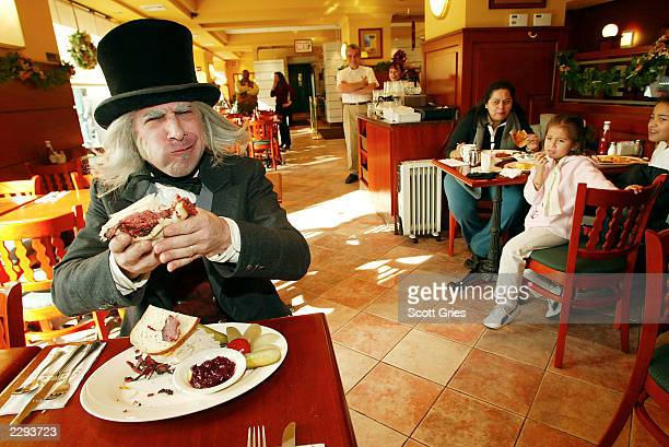 Ebenezer Scrooge from Radio City Entertainment's A Christmas Carol creates and enjoys the Scrooge Sandwich at the Stage Door Deli in New York City A...