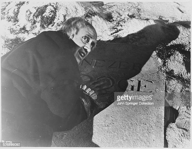 Ebenezer Scrooge leans on his own grave marker horrified at what may become if he doesn't change his ways in A Christmas Carol 1951