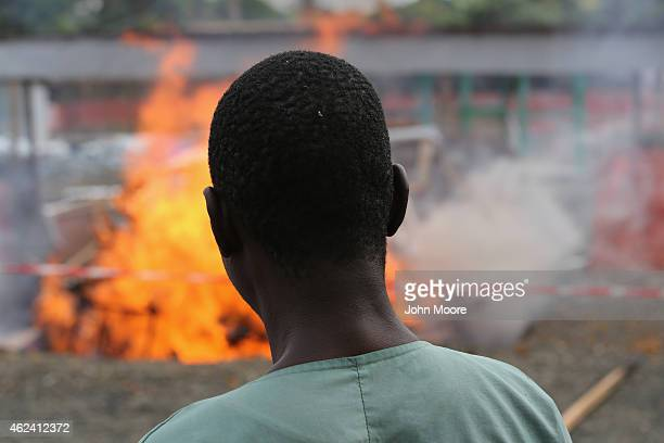 Ebola survivor Jessy Amos and now an employee of Doctors Without Borders watches after lighting fire to part of the Ebola Treatment Unit on January...