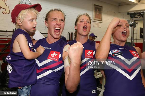 Ebony Antonio, Leah Mascall and Stephanie Cain of the Dockers sing the club song after winning the round five AFLW match between the Fremantle...