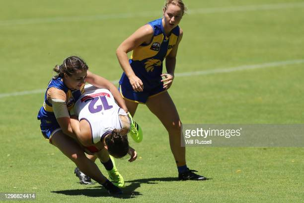 Ebony Antonio of the Dockers is tackled by Brianna Green of the Eagles during an AFLW pre-season match between the West Coast Eagles and the...