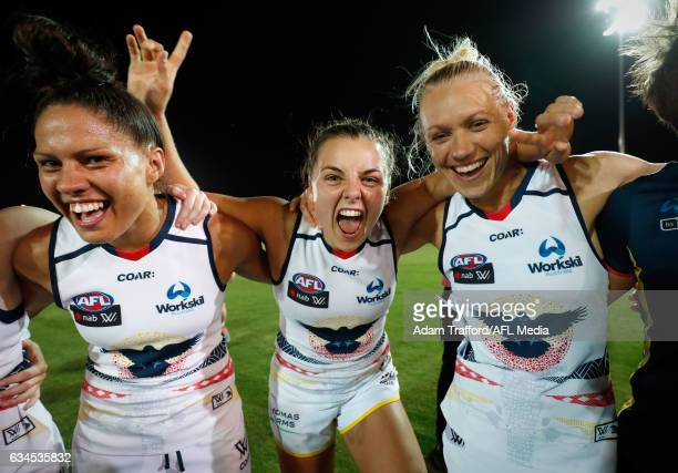 Ebony Marinoff of the Crows sings the team song with Stevie-Lee Thompson and Erin Phillips of the Crows during the 2017 AFLW Round 02 match between...