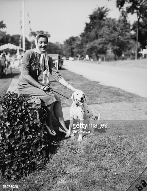 Eccentric American model and singer Edith Bouvier Beale sits on a low wall and pets her Dalmation Easthampton New York July 28 1944 Miss Beale and...
