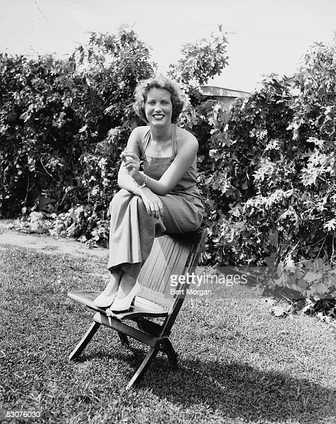 Eccentric American model and singer Edith Bouvier Beale sits on the back of a beach chair and smokes a cigarette Village Fair at Easthampton New York...