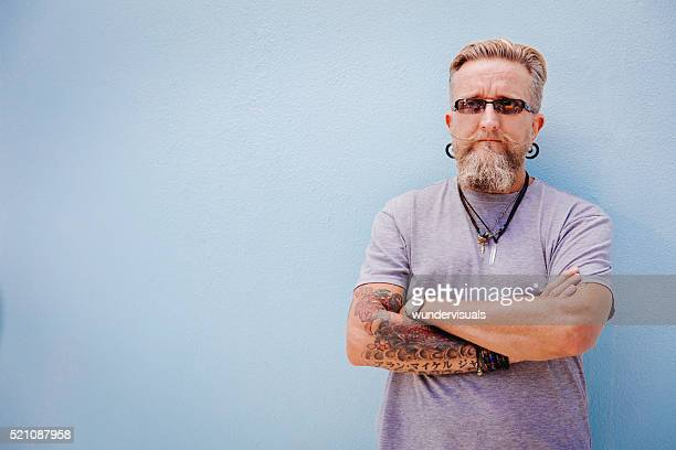 Eccentric mature man with tattoo and earrings