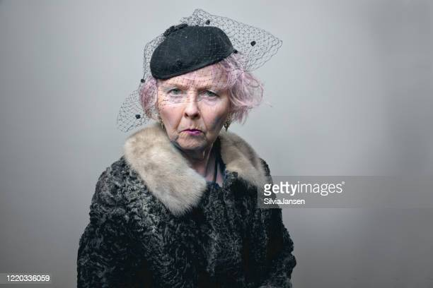 eccentric retro styled senior woman with pink hair - fur coat stock pictures, royalty-free photos & images