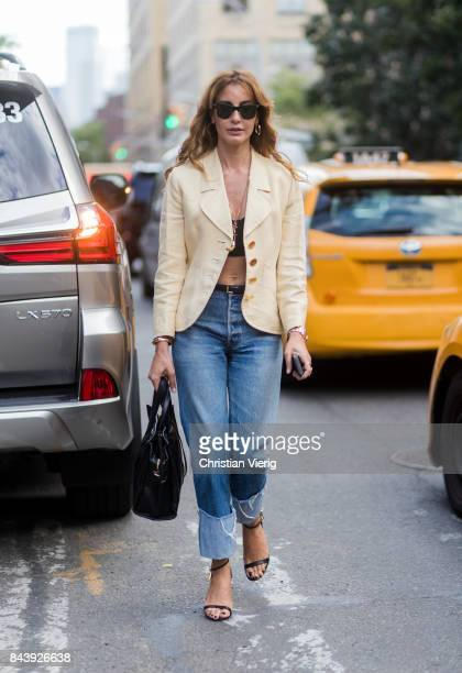 Ece Sukan seen wearing a cropped top, blazer jacket, two tone denim jeans, Prada bag, heels in the streets of Manhattan outside Creatures of Comfort...