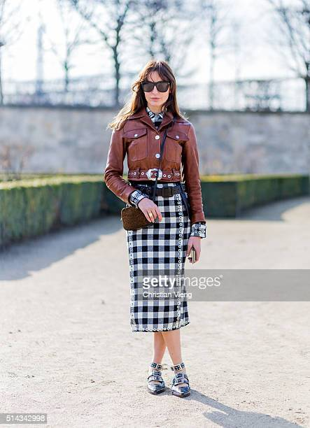 Ece Sukan wearing a black white plaid dress and a brown leather jacket outside Elie Saab during the Paris Fashion Week Womenswear Fall/Winter...