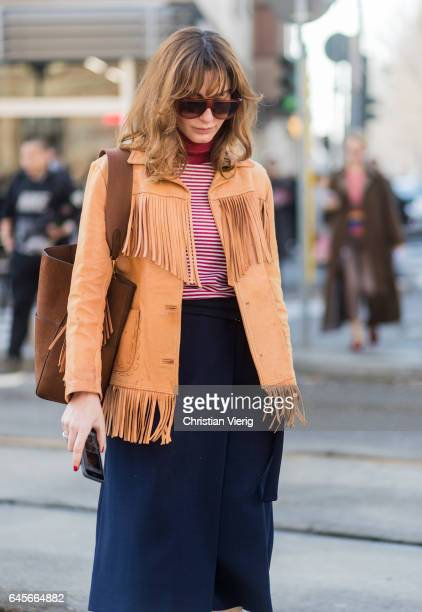 Ece Sukan wearing a brown jacket with fringes, blue skirt, beige overknees outside Marni during Milan Fashion Week Fall/Winter 2017/18 on February...