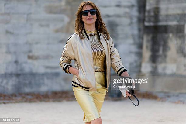 Ece Sukan wearing a golden jacket skirt and Chanel shoes outside Elie Saab on October 1 2016 in Paris France