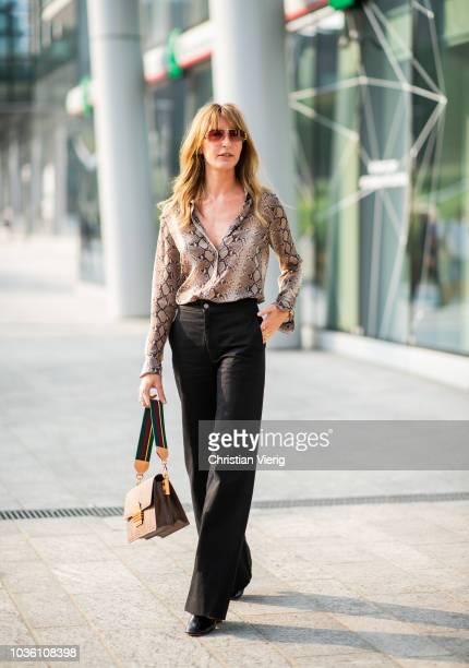 Ece Sukan wearing snake print top flared black pants bag is seen outside Alberta Ferretti during Milan Fashion Week Spring/Summer 2019 on September...