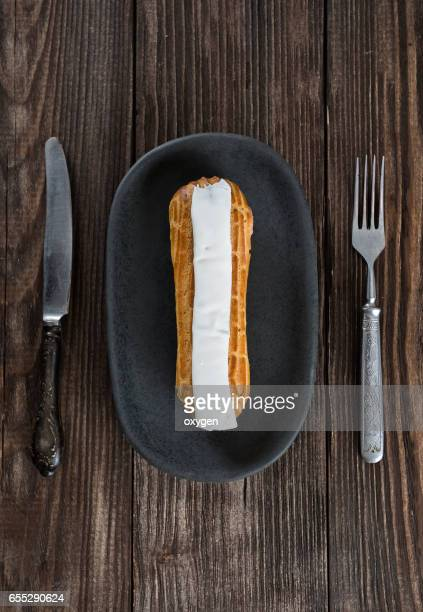 Eclair on dark wooden table
