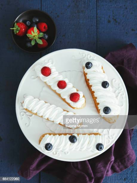 Eclairs with whipped cream and berries