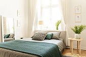 Eco cotton linen and blanket on a bed in nature loving family guesthouse for spring and summer vacation. Real photo.