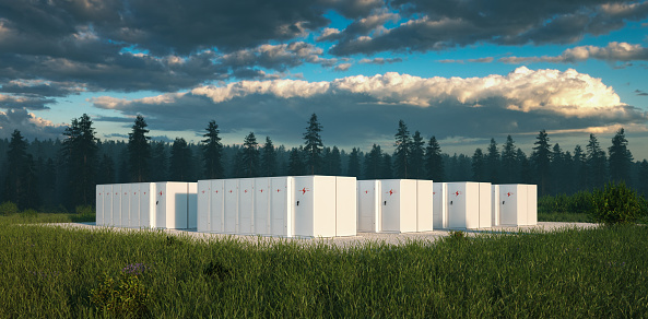 Eco friendly battery energy storage system in nature with misty forest in background and fresh grassland in foreground. 3d rendering. 1177095707