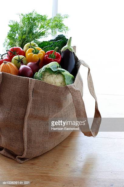 Eco friendly shopping bag filled with vegetables on table