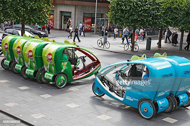 ecocabs in o'connell street, dublin, ireland - rickshaw stock photos and pictures