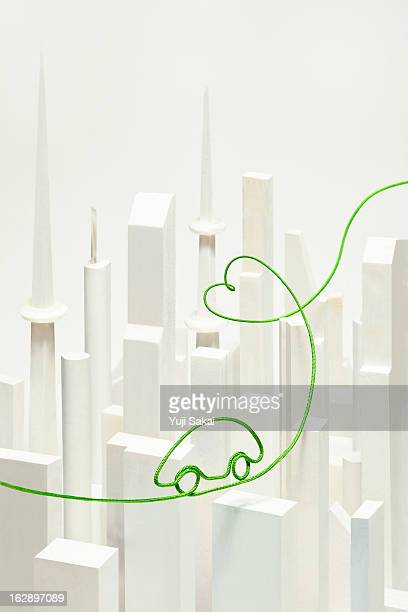eco-car shaped electric cord over  white buildings